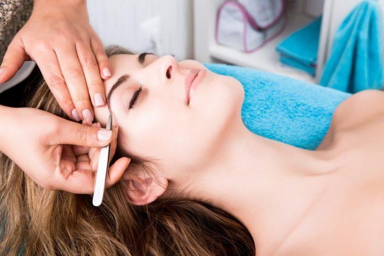 Woman getting tweezing eyebrow