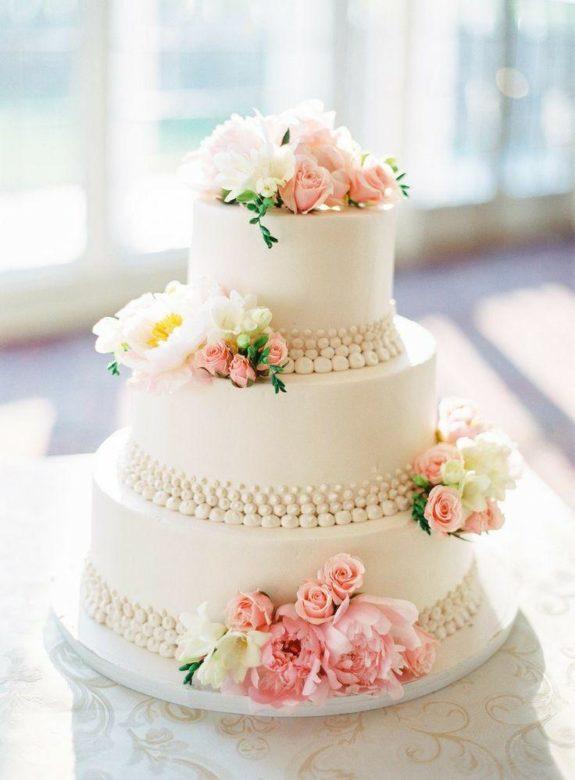 Torta nuziale con fiori rosa e bianchi