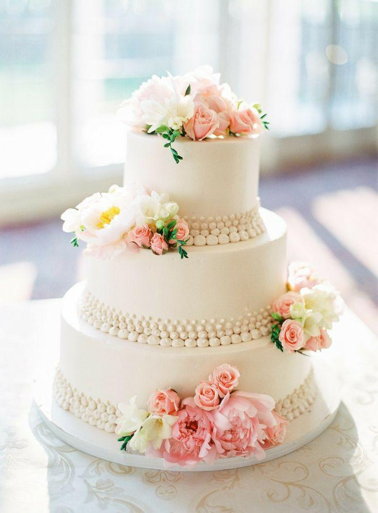 Torta nuziale con fiori rosa e bianchi. La