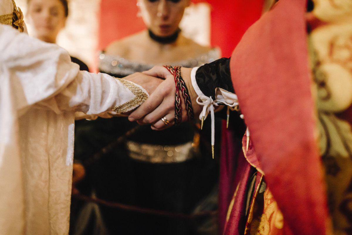 Il rituale dell'handfasting (mani degli sposi legate da una benda) durante il matrimonio medievale di Roberta e Alessandro