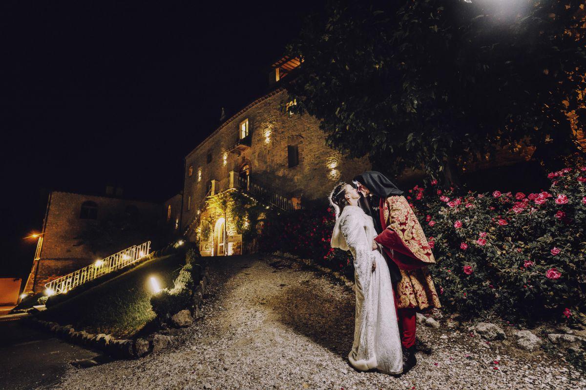 Il matrimonio medievale di Alessandro e Roberta. Alle spalle dei due sposi, la facciata principale del Castello di Montignano, la loro location wedding