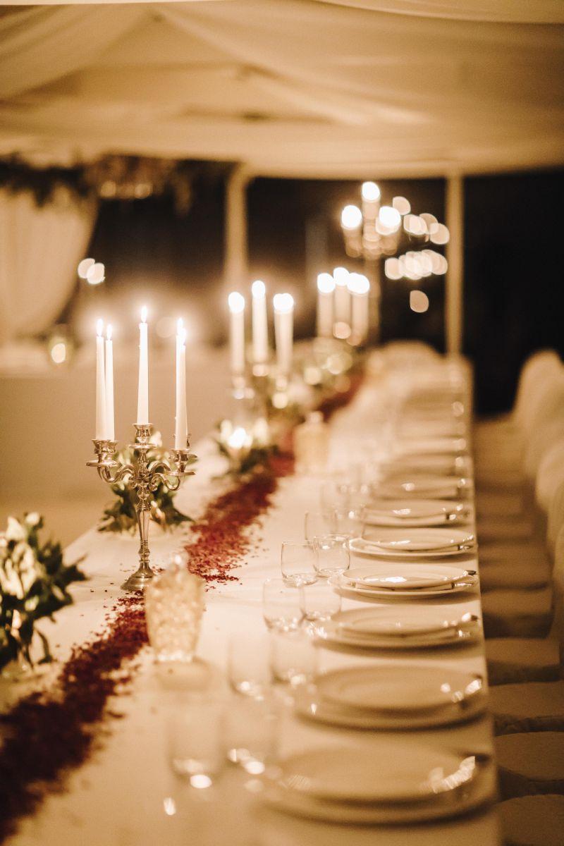 Il banchetto medievale di Alessandro e Roberta: tovagliato di lino bianco, candele e runner di fiori secchi profumati per poggiare le pentole calde