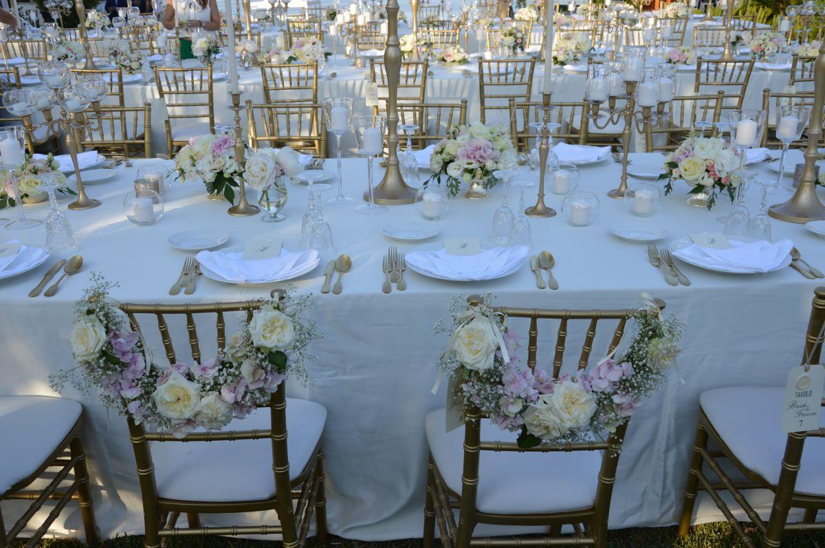 Le sedute degli sposi Maria Pia e Salvo decorate dai fiori. Dettaglio della mise en place tutta nei toni dell'oro