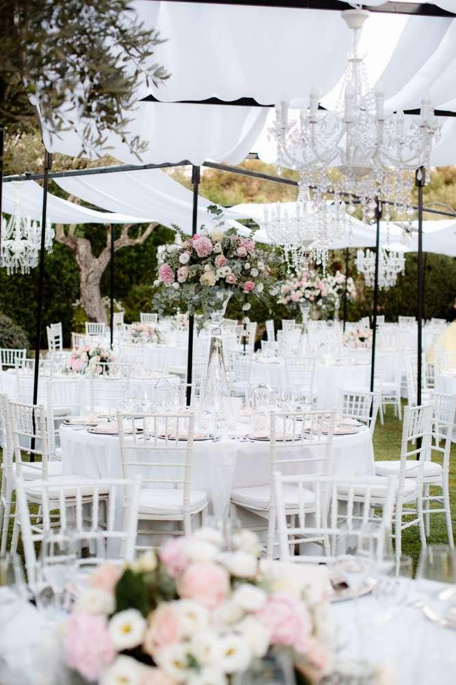 Tavoli, sedie e tendaggi bianchi alle nozze in un giardino di Francesco e Francesca