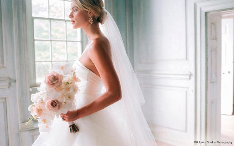 In questa foto una sposa nel giorno del matrimonio posa davanti ad una finestra con il busto rivolto a sinistra tenendo in mano il suo bouquet di fiori rosa e bianchi