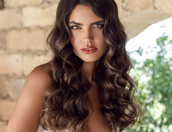 In questa foto una modella con capelli ricci posa indossando un trucco sposa di Orazio Tomarchio La Truccheria Cherie con rossetto rosso lucido. Sugli occhi e sul viso il truccatore ha usato toni naturali