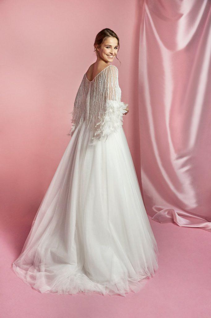 In questa foto un abito da sposa Carlo Pignatelli 2021 color bianco e con dettagli di piume sulle maniche