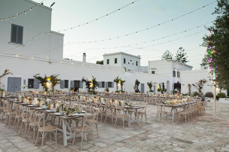 In questa foto, lunghi tavoli imperiali allestiti per un matrimonio negli spazi esterni di Masseria San Nicola, a Savelletri, in Puglia