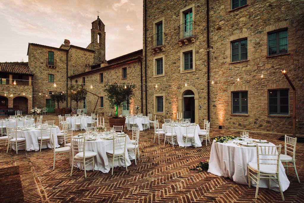 In questa foto la terrazza di Spao Borgo San Pietro, in Umbria, allestita per un matrimonio con tavoli rotondi e fili di luci sospese in cielo