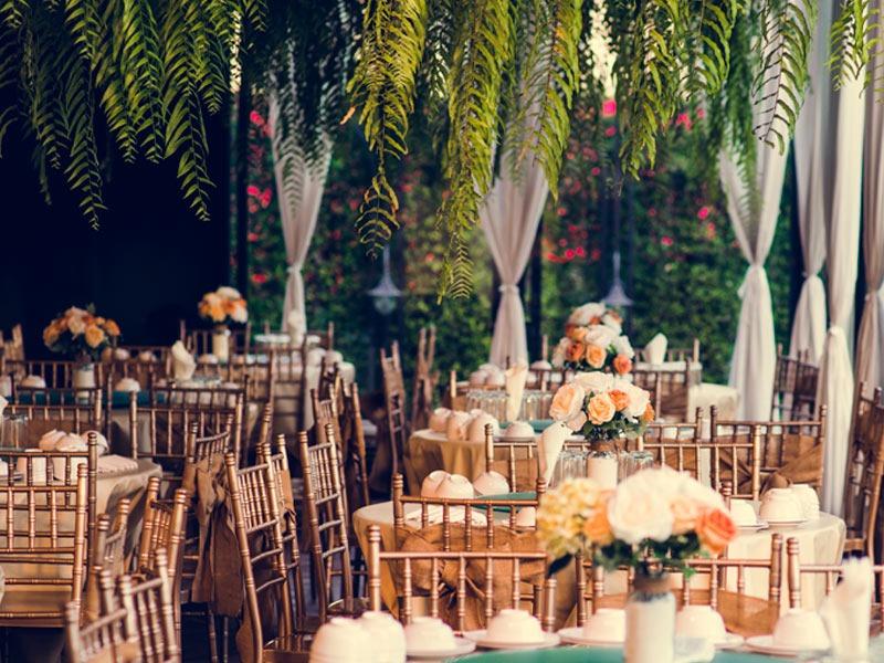 In questa foto una location per matrimonio allestita con tavoli rotondi e decorazioni aeree vegetali