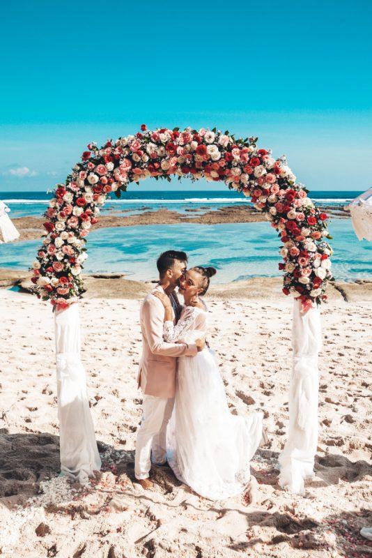 Nella foto due sposi abbracciati mentre celebrano il loro matrimonio sulla spiaggia