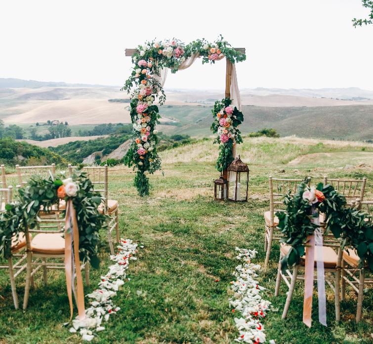 Nella foto un arco di legno e fiori e le sedie disposti per celebrare un matrimonio con rito civile in un bosco
