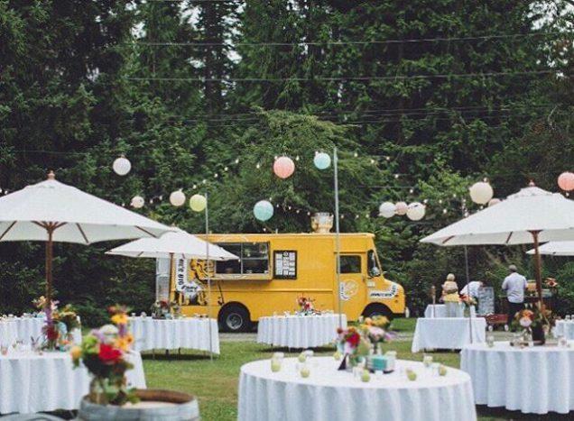 In questa foto un allestimento nuziale all'aperto, con tavoli rotondi per gli ospiti e un food truck giallo per servire il cibo
