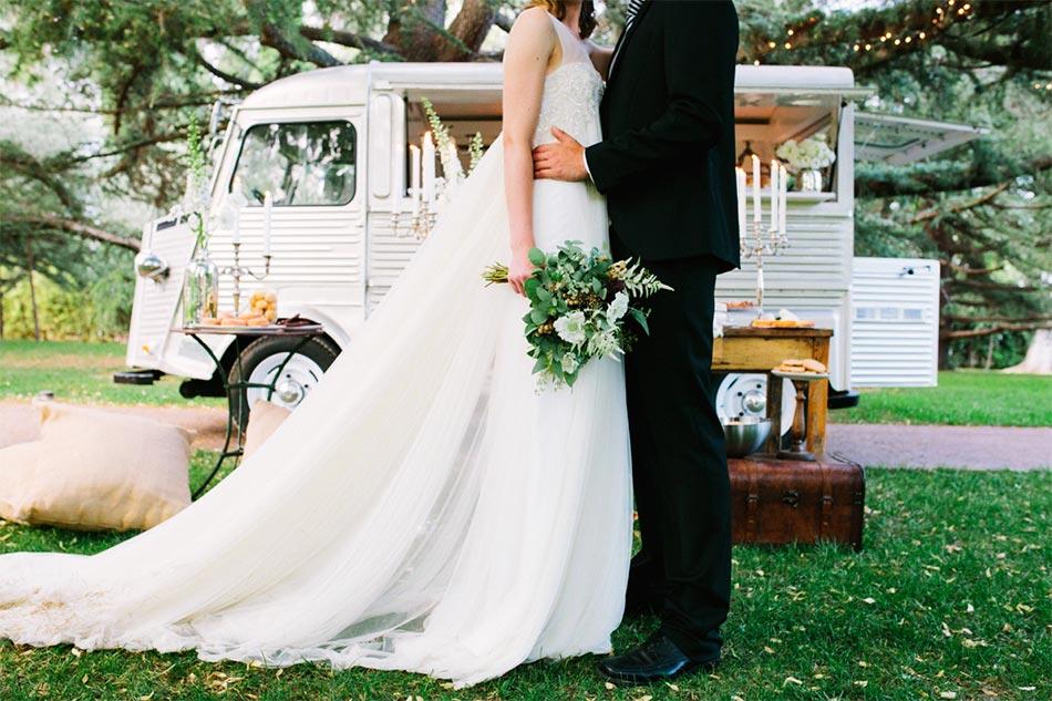 In questa foto due sposi e sullo sfondo un food truck vintage per il loro ricevimento di nozze