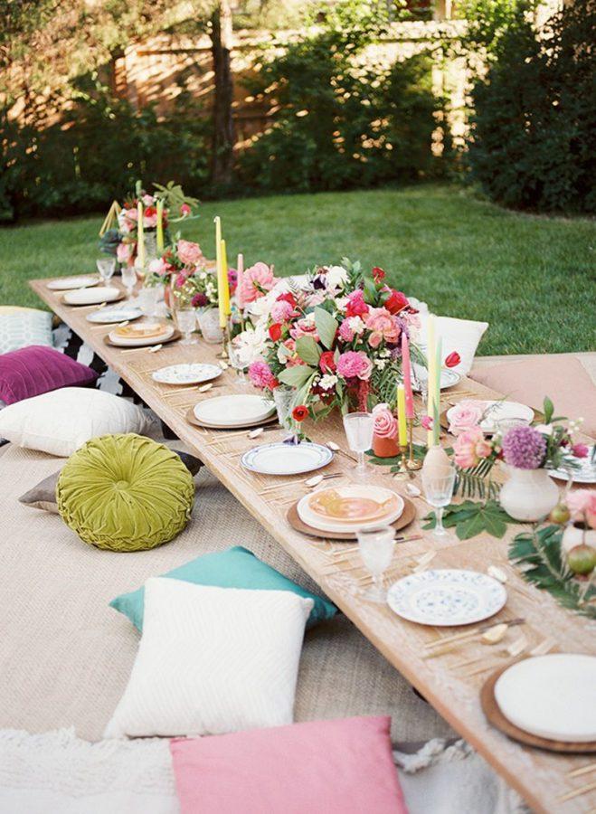 Nella foto un tavolo imperiale basso decorato con fiori e stoviglie colorate, ai suoi lati maxi cuscini di diversi colori e stuoie come sedute per gli ospiti