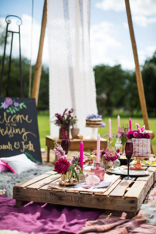 In questa foto un wedding pic nic in stile boho chic, con pallet in legno e tovaglie e decori super colorati
