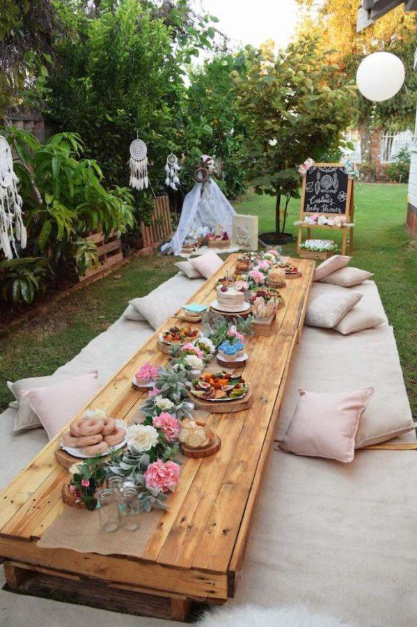 In questa foto un lungo tavolo imperiale basso e in legno e ai lati tovaglie e cuscini per far accomodare gli ospiti