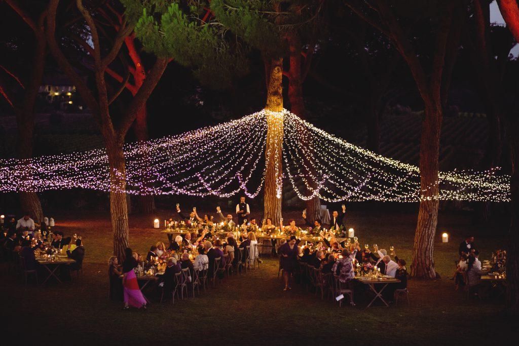 In quesa foto i fili di luci tra gli alberi creano un tetto illuminato sui tavoli del banchetto nuziale all'aperto