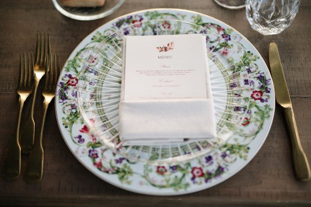 In questa foto un piatto in ceramica decorato con motivi floreali, utilizzato per una mise en place di nozze