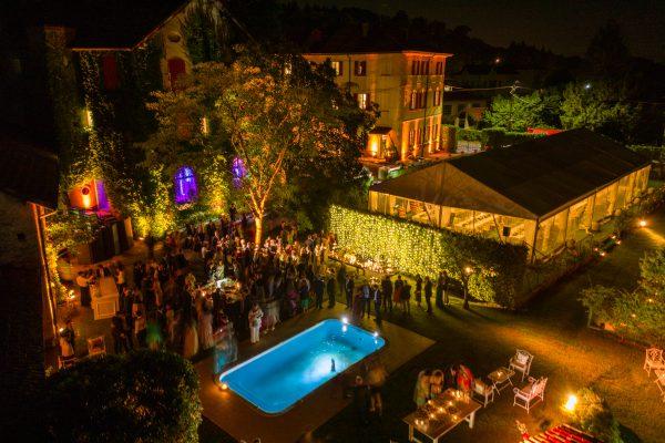 In questa foto una veduta dall'alto serale di una location illuminata e allestita per ospitare un ricevimento nuziale