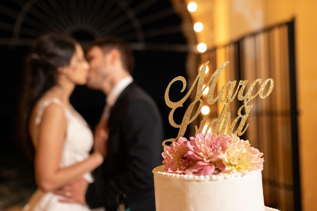 In questa foto in primo piano il cake topper sulla torta nuziale e di sfondo gli sposi mentre si baciano