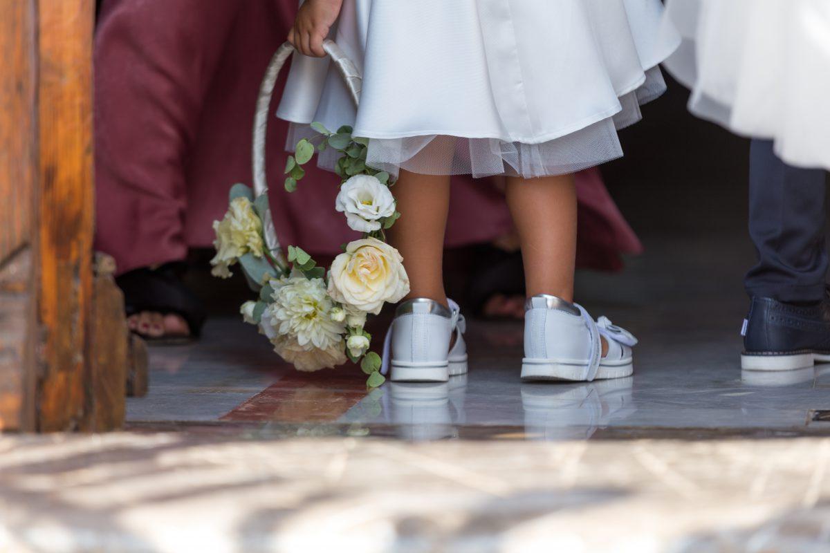 In questa foto una piccola damigella in sneakers prima dell'ingresso in chiesa di una sposa che si è affidata ad Antonella Candido Wedding Planner
