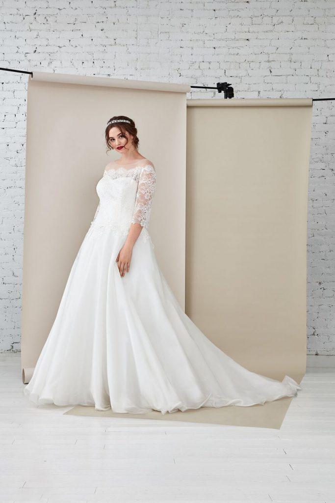 In questa foto un modello con maniche in pizzo proposto tra gli abiti da sposa curvy Atelier Emé