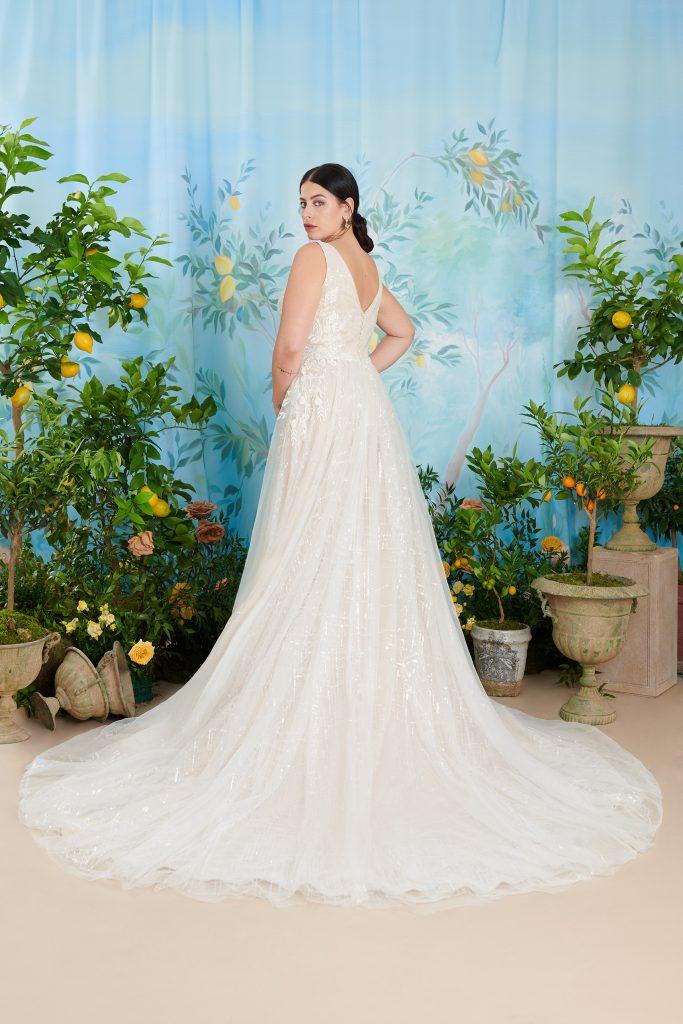In questa foto una modella indossa uno degli abiti da sposa curvy atelier emé con scollo sulla schiena