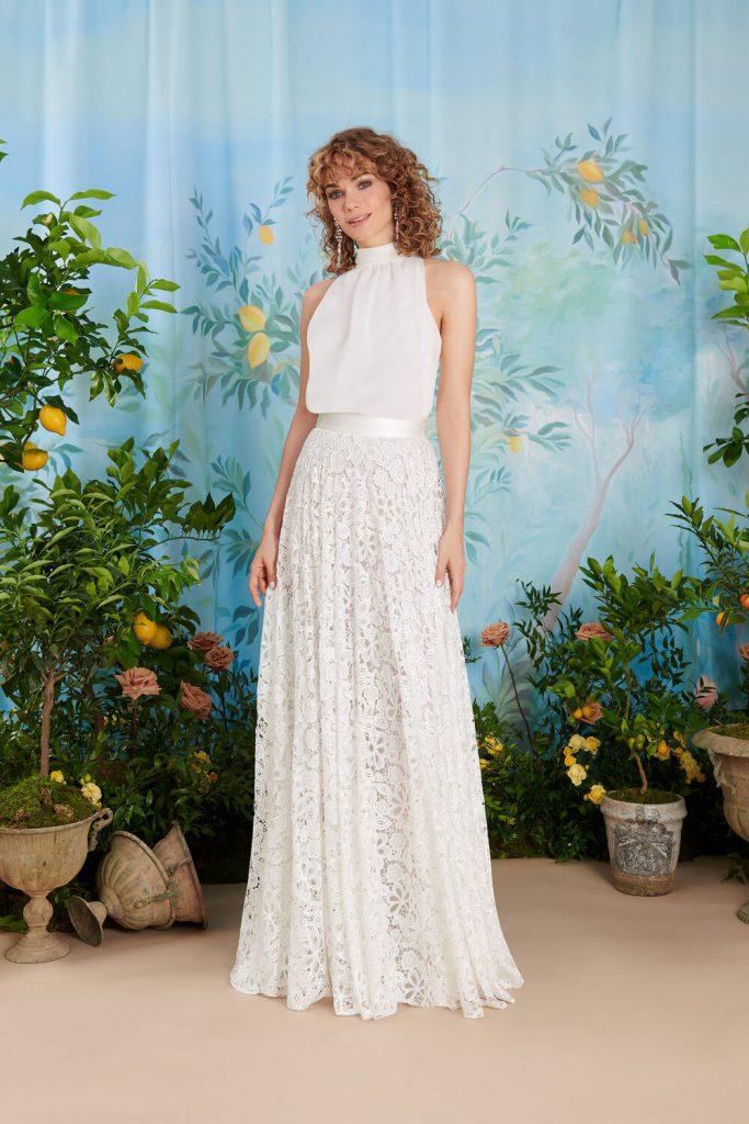In questa foto una modella indossa uno degli abiti da sposa Atelier Emé per rito civile con gonna in pizzo