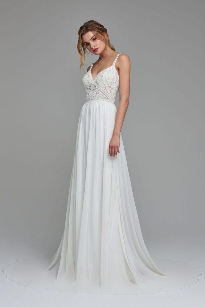 In questa foto una modella indossa uno degli abiti da sposa Atelier Emé per rito civile con corpetto in pizzo
