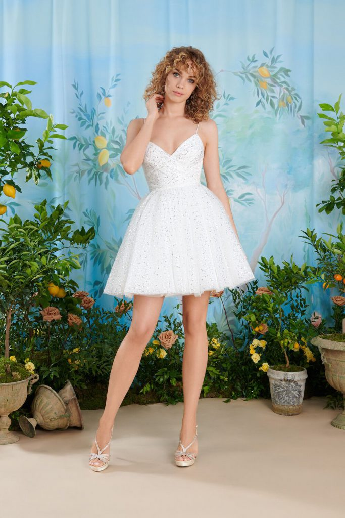 In questa foto una modella indossa uno degli abiti da sposa Atelier Emé per rito civile con gonna corta