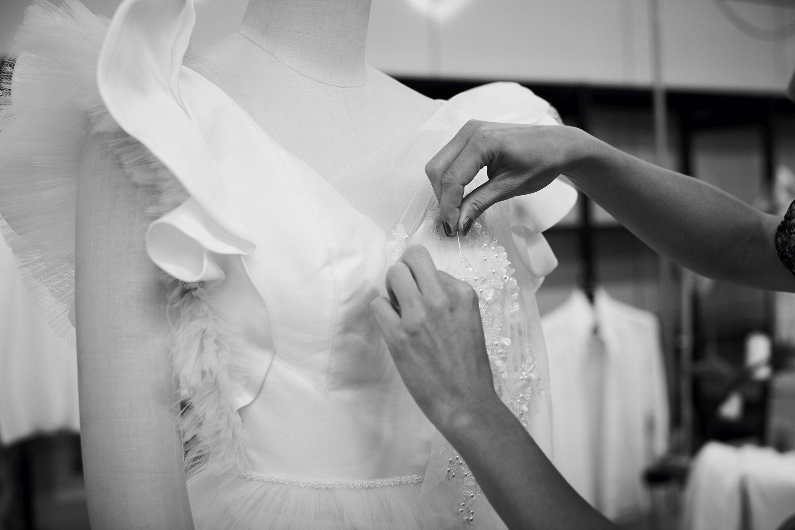 In questa foto le mani di una sarta al lavoro sulla scollatura di un abito da sposa Carlo Pignatelli: sono il simbolo perfetto di #FattoinItalia