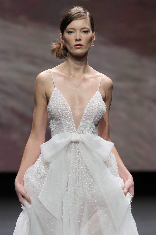 In questa foto un abito da sposa di Leonie Bridal con scollo a V e maxi fiocco