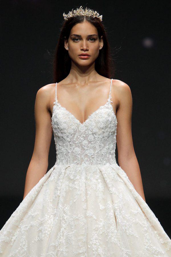 In questa foto una modella indossa una coroncina di Swarovsky insieme ad un abito da sposa Demetrios 2021
