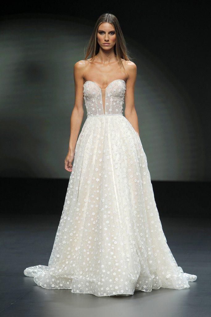 In questa foto una modella sfila sulla passerella della Valmont Barcelona Bridal Fashion Week indossando un abito da sposa Pronovias 2021