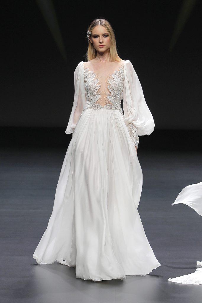 In questa foto una modella indossa un abito da sposa Pronovias con leggere maniche a palloncino durante la sfilata alla VBBFW20