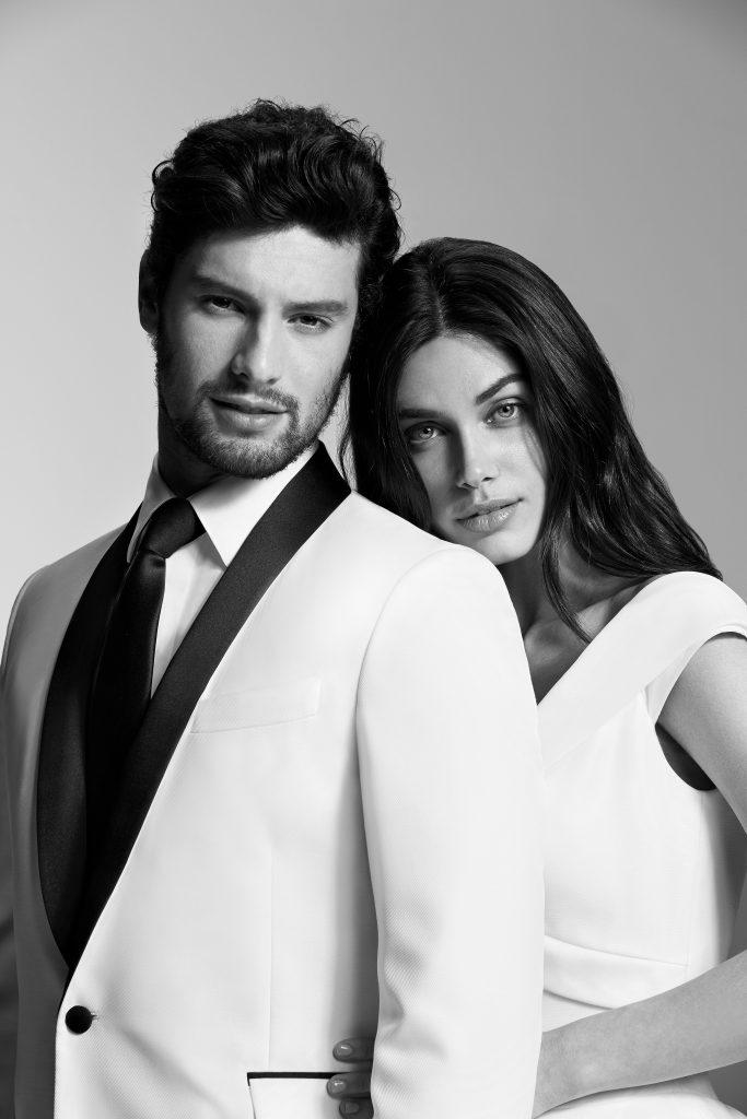 In questa foto due modelli abbracciati: lui indossa un abito Carlo Pignatelli for Pronovias, lei un vestito da sposa Pronovias
