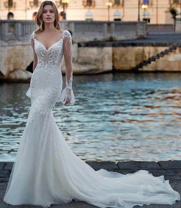 In questa foto un abito da sposa in pizzo con scollo profondo Nicole Spose 2021