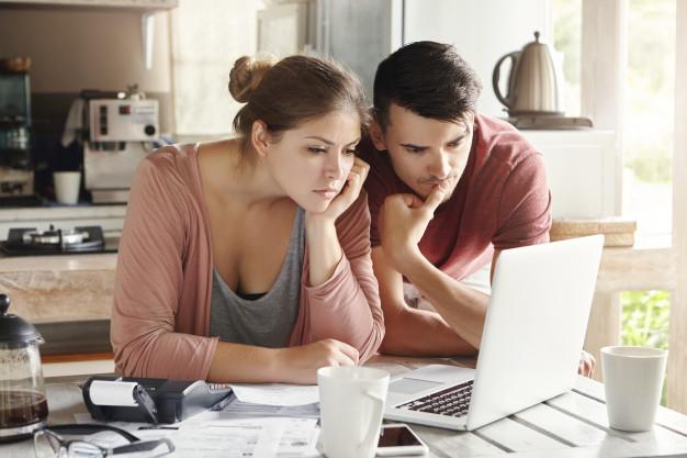In questa foto una coppia davanti al computer intenta a far quadrare i conti del budget per il matrimonio