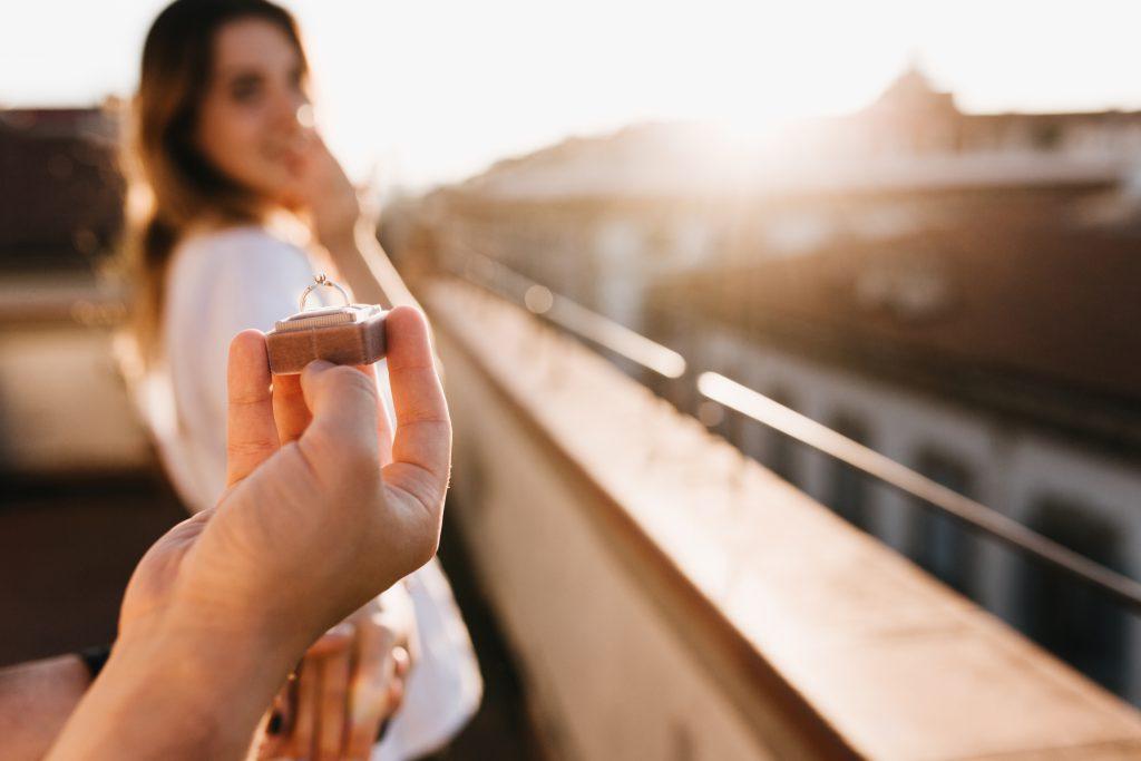 In questa foto un uomo chiede alla sua compagna di sposarlo in una giornata di sole, all'aperto.
