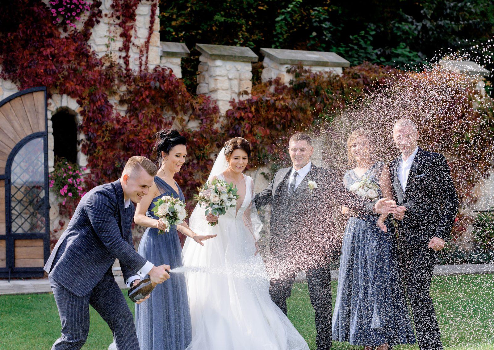 In questa foto una coppia di sposi festeggia con alcuni degli invitati al matrimonio