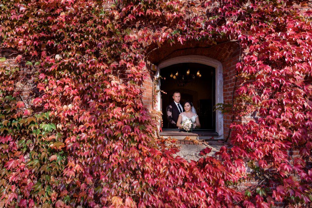 In questa foto una coppia affacciata alla finestra di un castello per matrimoni