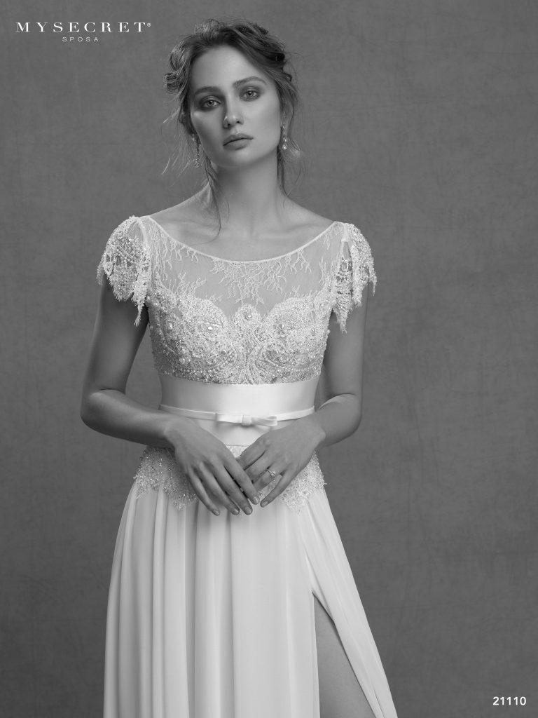 In questa foto una modella indossa un abito da sposa con corpetto in pizzo di My Secret Sposa