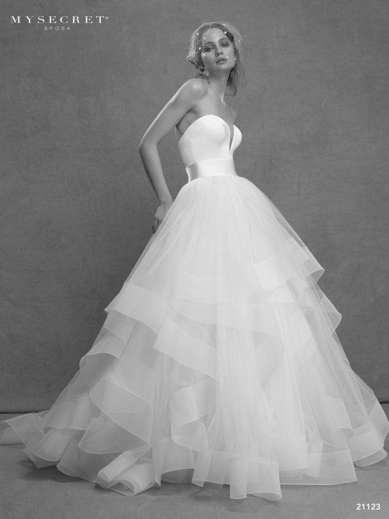 In questa foto una modella indossa un abito da sposa con gonna vaporosa a balze di tulle della linea My Secret Sposa