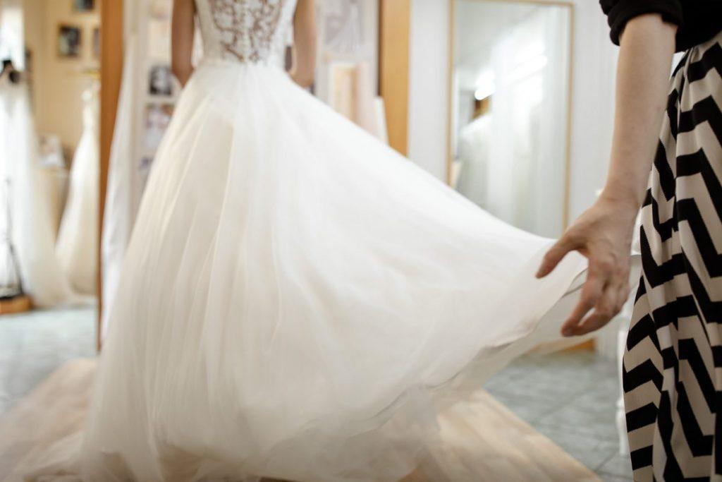 In questa foto una stilista dell'atelier Couture Hayez apre la gonna di un abito da sposa per mostrarne ampiezza e leggerezza