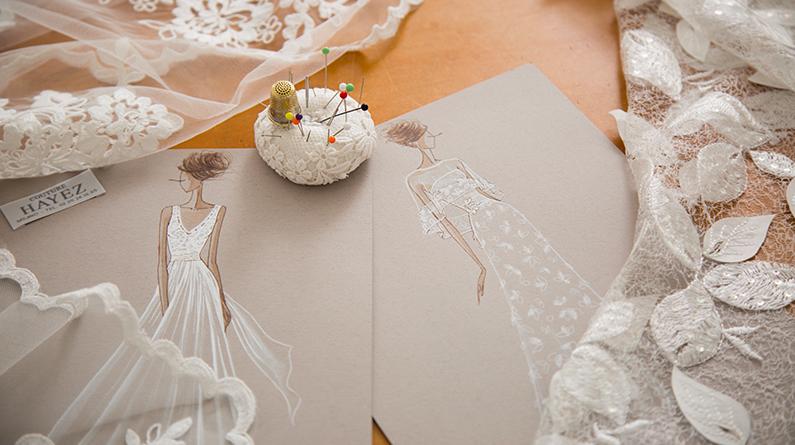 In questa foto due bozzetti firmati Atelier Couture Hayez su un tavolo, tra tessuti e spille per cucire