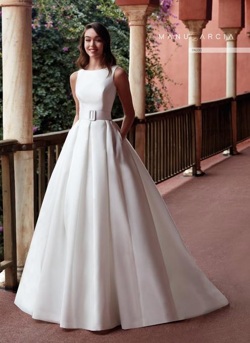 In questa foto una modella indossa un abito da sposa redingote della linea Manu Garcia