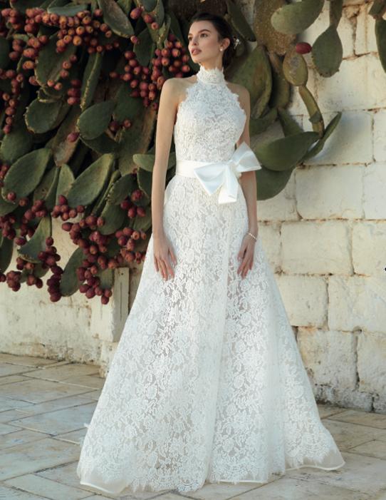 In questa foto una modella indossa un abito da sposa con collo alto di Blumarine Bridal