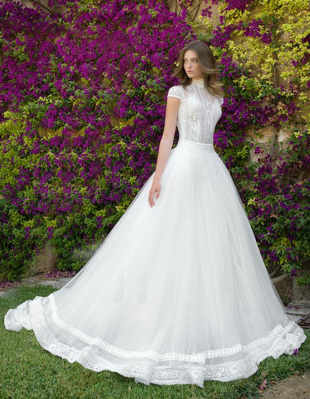 In questa foto una modella indossa un abito da sposa con collo alto e mezze maniche della collezione Nadia Orlando
