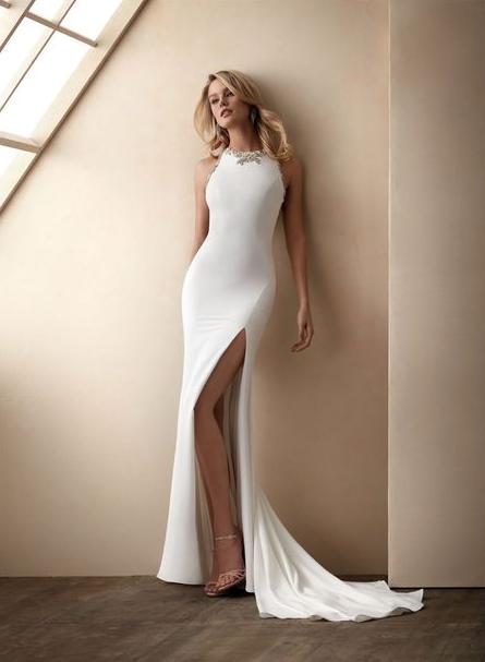 In questa foto una modella indossa un abito da sposa a sirena con scollatura gioiello di Valerio Luna